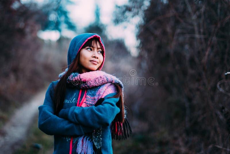 Junges Schönheitsporträt in tragender Strickjacke des kühlen Wetters und im bunten Schal während des Nachmittages draußen stockbilder