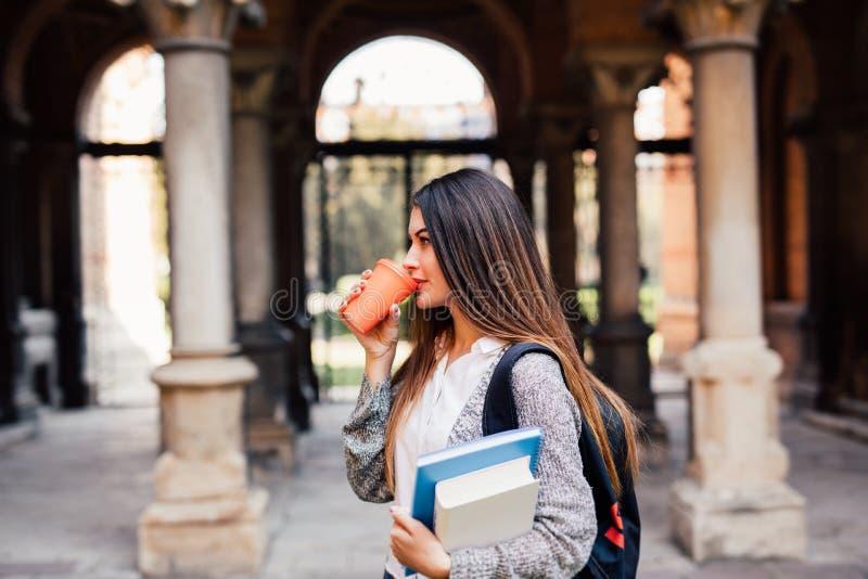 Junges Schönheitsstudentenmädchen mit Notizbüchern draußen das Hochschulgetränk ein Tasse Kaffee lizenzfreie stockfotos