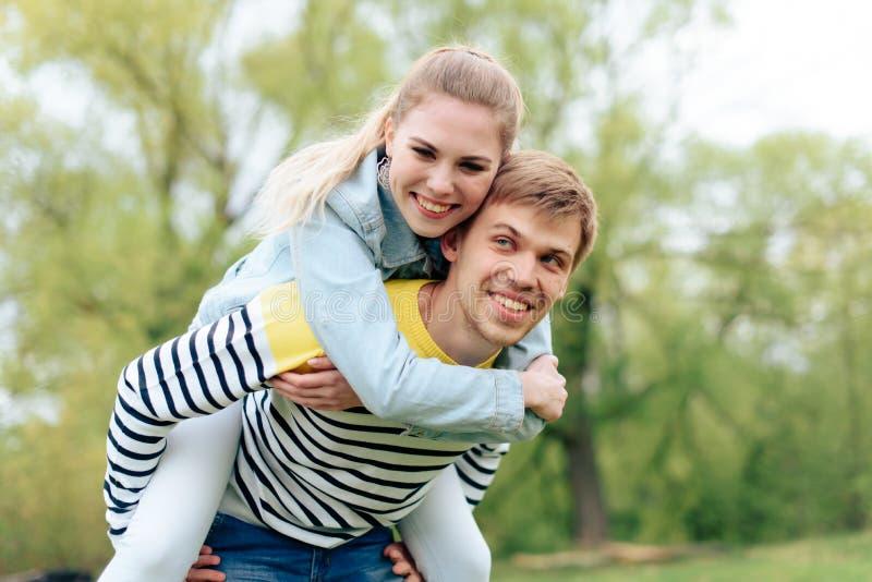 Junges sch?nes M?dchen auf der R?ckseite eines jungen Mannes drau?en in Sommer 1 lizenzfreies stockbild