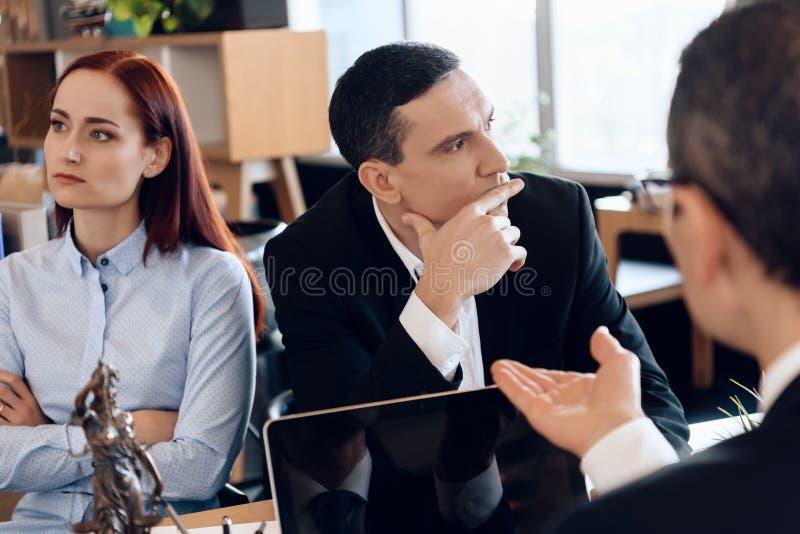 Junges Scheidungspaar schaut in den verschiedenen Richtungen und hört auf Rechtsanwalt, der bei Tisch sitzend stockfotografie