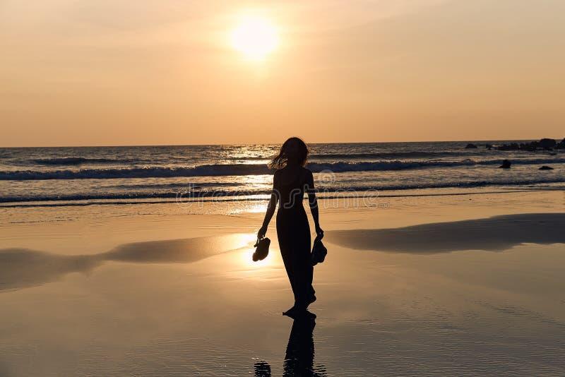 Junges schlankes Mädchen, das entlang den sandigen Strand auf dem Hintergrund des Sonnenuntergangs und des Meeres geht lizenzfreies stockbild