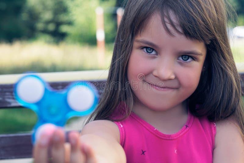 Junges Schulmädchen, das populäres Unruhespinnerspielzeug hält Glückliches lächelndes Kind, das mit Spinner spielt lizenzfreies stockbild