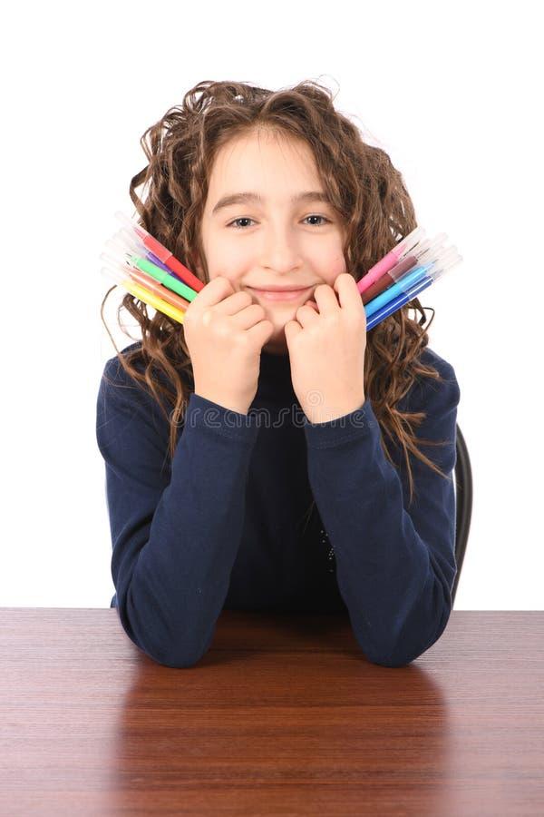 Junges Schulmädchen zeichnet mit Markierungen beim bei Tisch sitzen stockbild