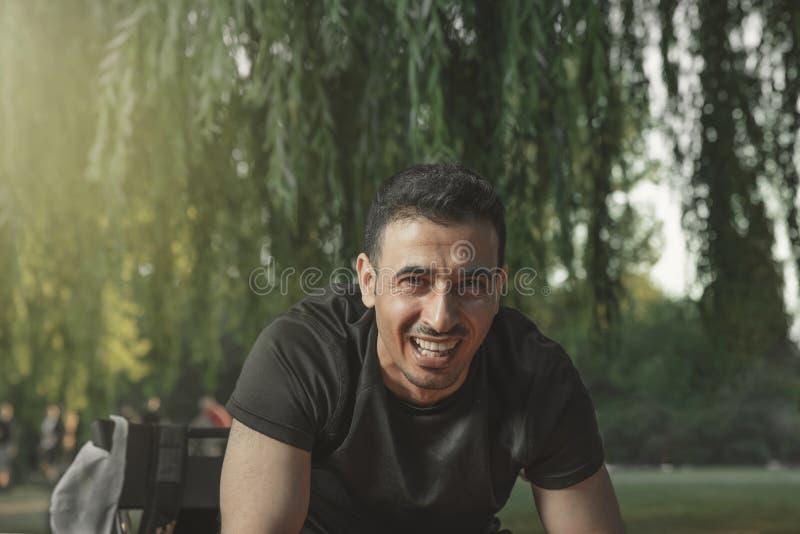 Junges schwarzes behaartes arabisches Mannlachen, das lachend vor ihm in einem Sommerpark schaut stockbild