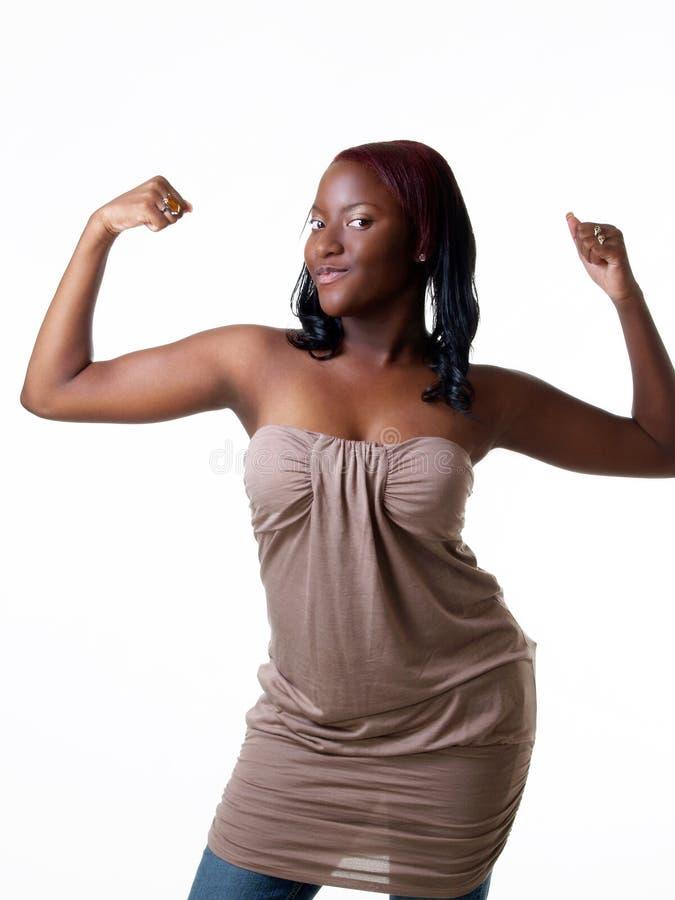 Junges schwarzes jugendlich Mädchen, das ihren zweiköpfigen Muskel zeigt lizenzfreie stockbilder