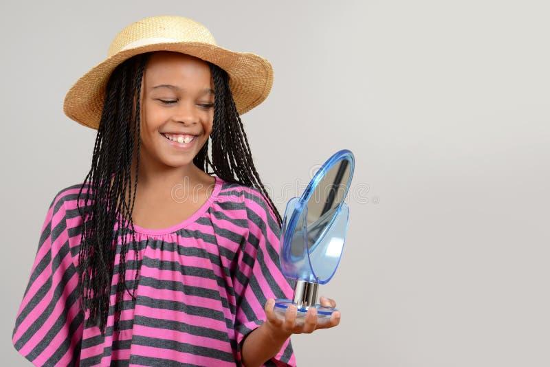 Junges schwarzes Mädchen, das auf Strohhut versucht lizenzfreie stockbilder