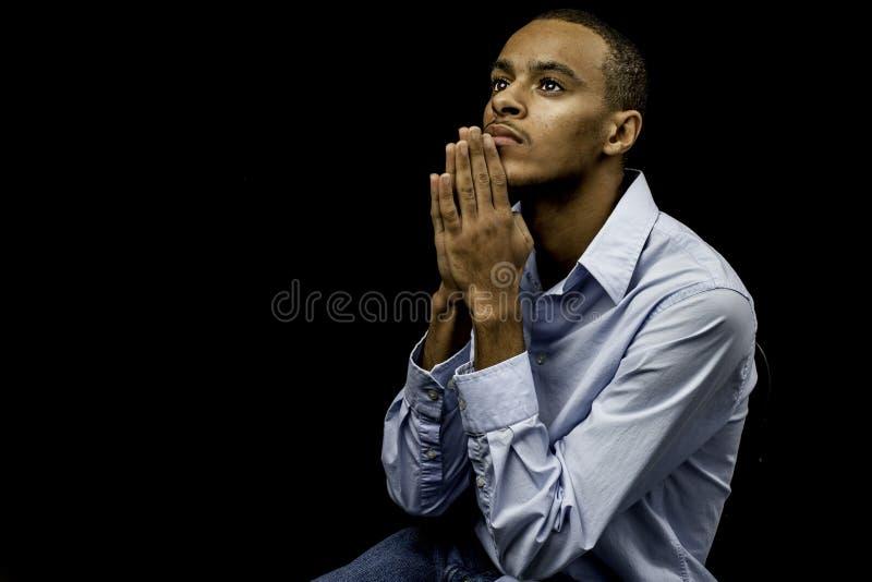 Junges schwarzes männliches Beten stockfoto