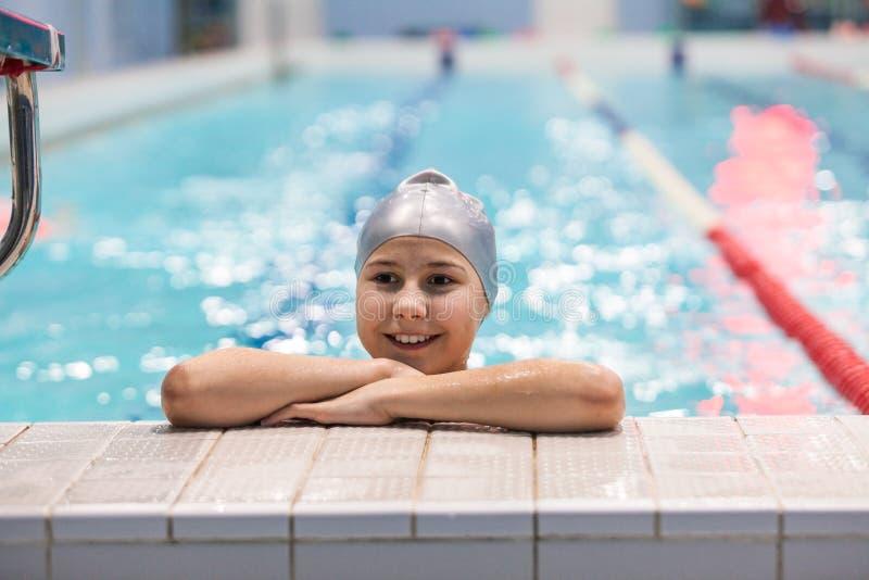 Junges Schwimmermädchen Porträt von zehn Jahren alten kaukasischen Athleten in der Schwimmenkappe im Pool stockfotografie