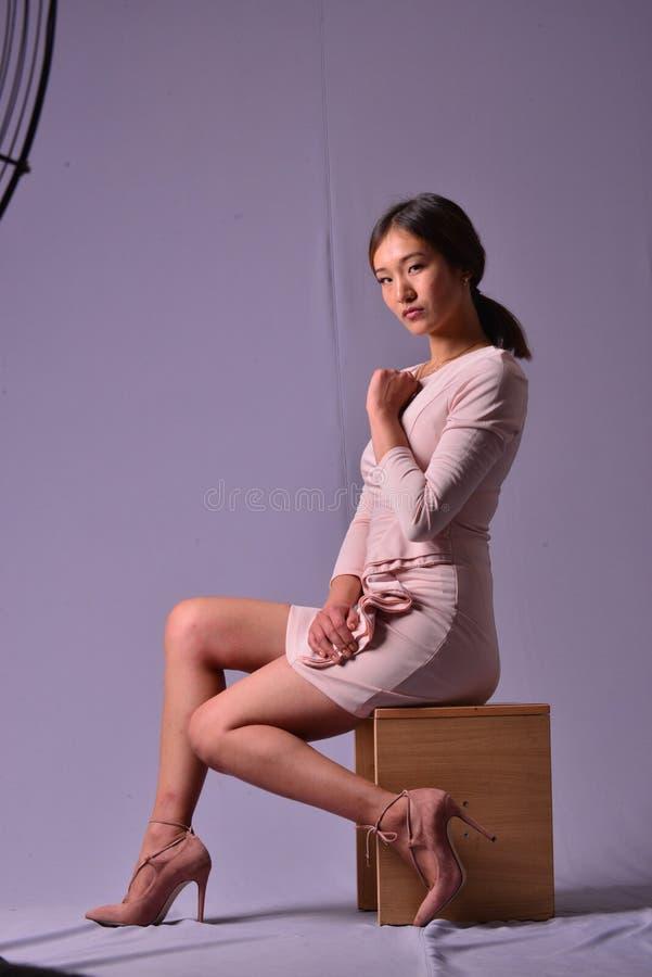 Junges sexuelles Modell, das auf einem Stuhl in einem purpurroten Kleid aufwirft im Studio sitzt lizenzfreie stockfotos