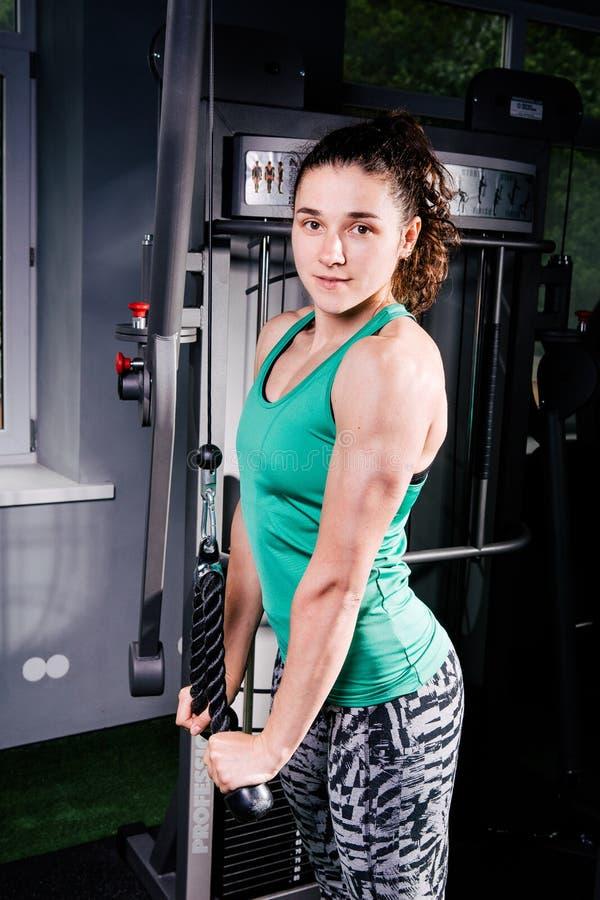 Junges sexy Eignungsfrauentraining mit Trainingsmaschine in der Turnhalle stockfoto