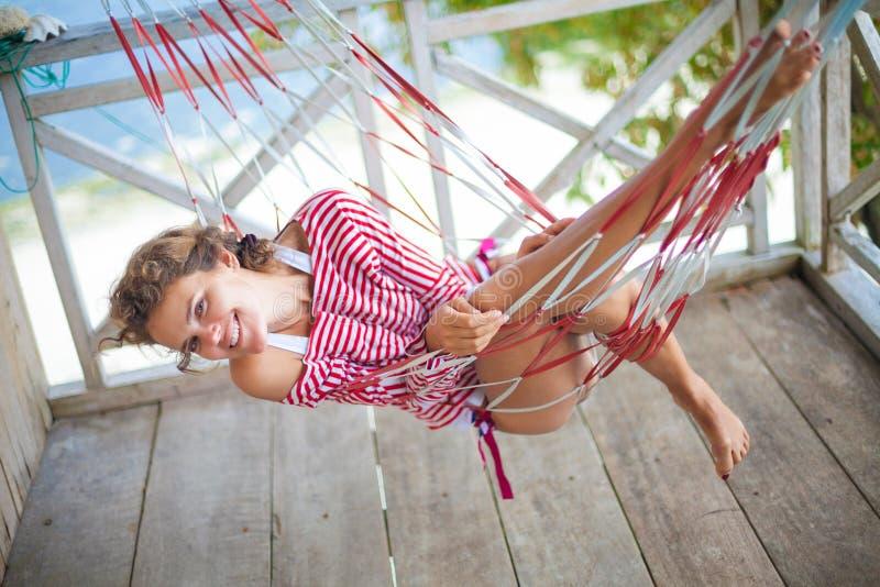 Junges sexy Mädchen des Fotos, das auf Strand Bungalow in der Hängematte sich entspannt Lächelnde Frau, die Sommer der Kühlzeit i stockbild