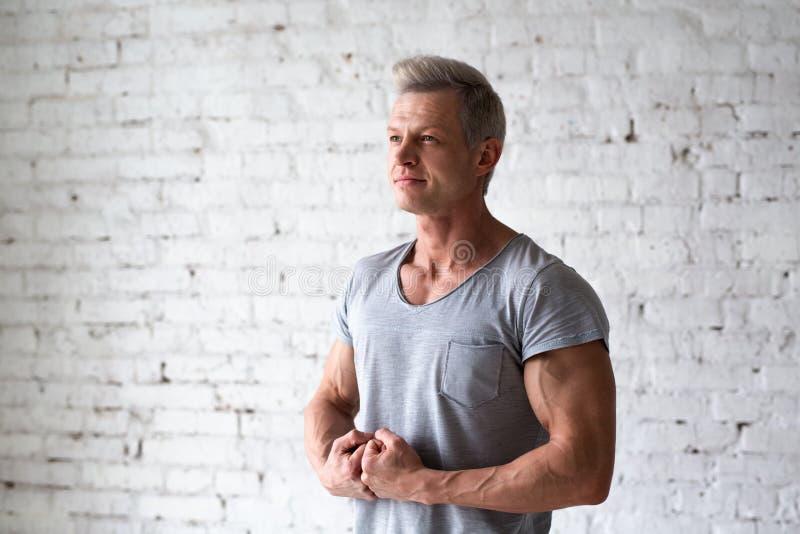 Junges sexy Mannbodybuilderathleten-Studioporträt im Dachboden auf dem Hintergrund der weißen Backsteinmauer Hübsches Kerlmodell  lizenzfreie stockbilder