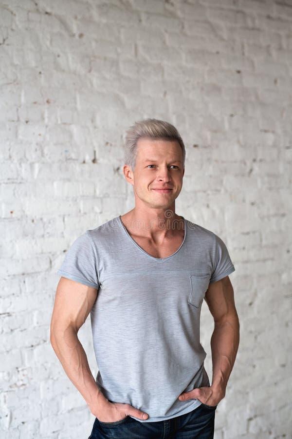 Junges sexy Mannbodybuilderathleten-Studioporträt im Dachboden auf dem Hintergrund der weißen Backsteinmauer Hübsches Kerlmodell  lizenzfreies stockbild