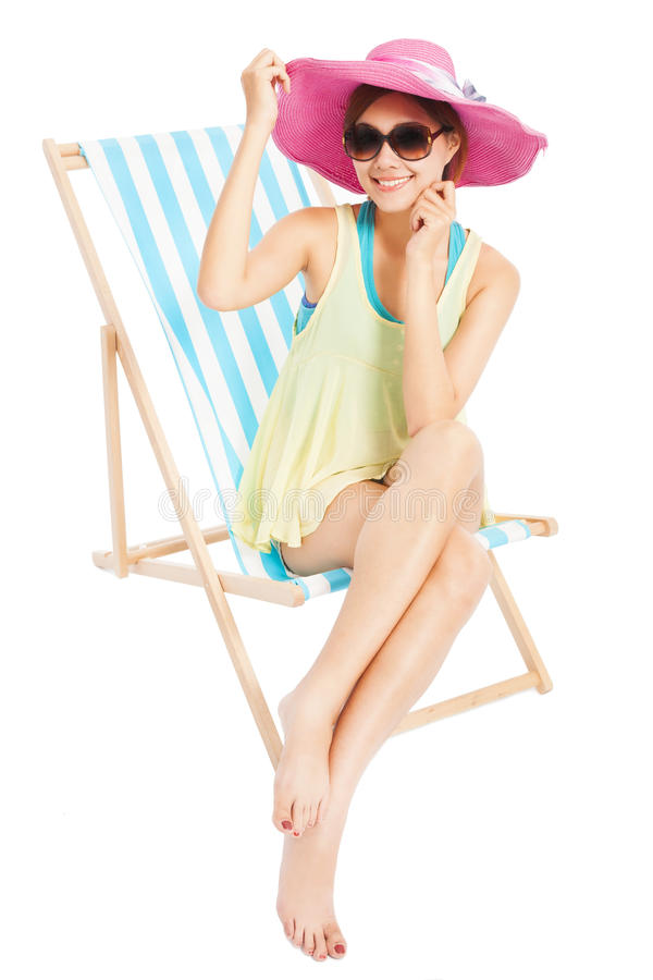 Junges Sonnenscheinmädchen, das auf einem Strandstuhl lächelt und sitzt stockfotos