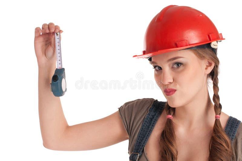 Junges spielerisches Arbeitskraftfrauenholding-Bandmaß lizenzfreie stockfotografie