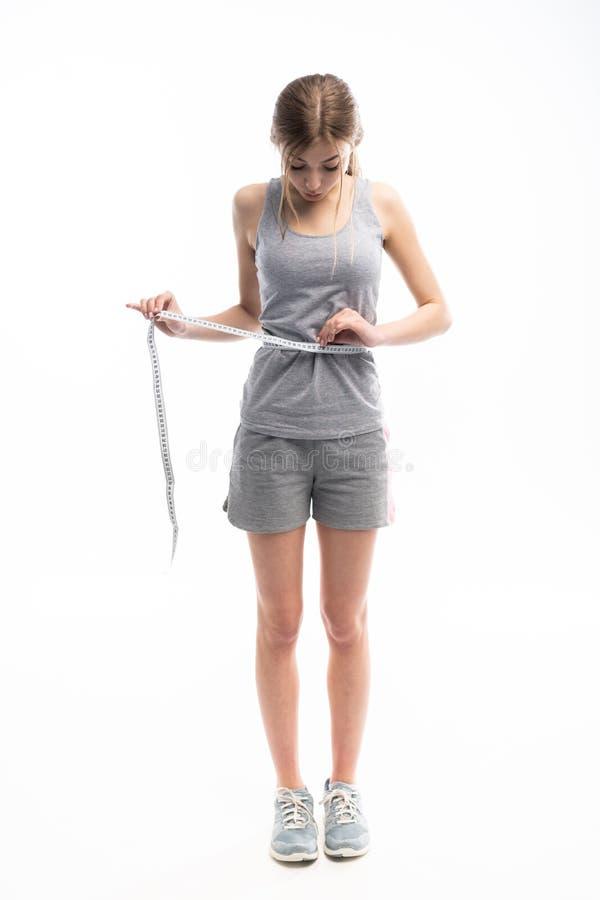 Junges, sportliches, geeignetes und schönes Mädchen mit dem messenden Band über weißem Hintergrund stockfotos