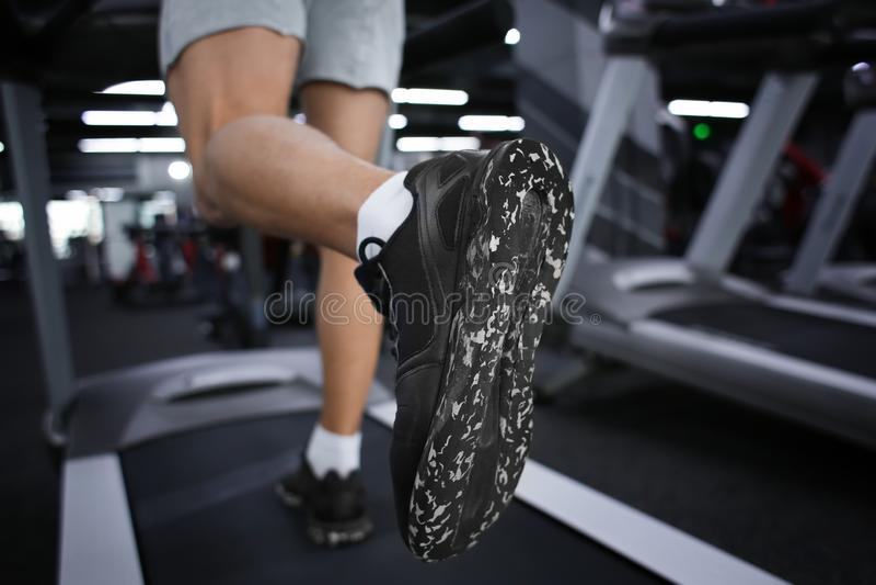 Junges sportliches Manntraining auf Tretmühle in der modernen Turnhalle, Nahaufnahme lizenzfreies stockfoto