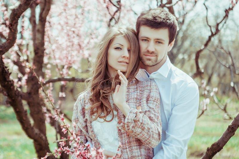 Junges stilvolles glückliches Paar in der Liebe, die in blühendem Garten umarmt Junge und Mädchen, die draußen stillstehen stockfoto