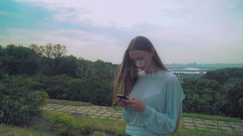 Junges stilvolles Mädchen, das auf einem Hügel steht und eine Mitteilung am Telefon gewinnt lizenzfreie stockfotografie