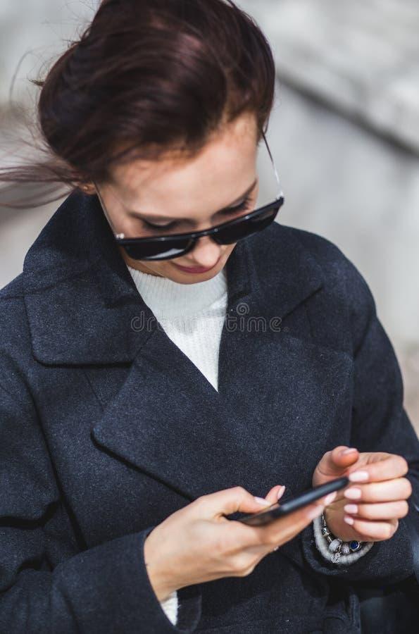 Junges stilvolles schönes brunette Mädchen in der Sonnenbrille, die den Smartphone, gehend auf Straße betrachtet lizenzfreies stockbild