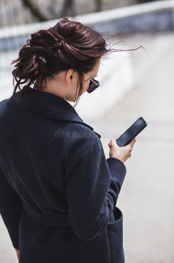 Junges stilvolles schönes brunette Mädchen in der Sonnenbrille, die den Smartphone, gehend auf Straße betrachtet lizenzfreie stockbilder