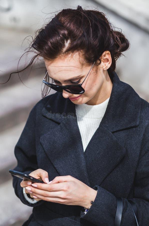 Junges stilvolles schönes brunette Mädchen in der Sonnenbrille, die den Smartphone, gehend auf Straße betrachtet lizenzfreie stockfotos