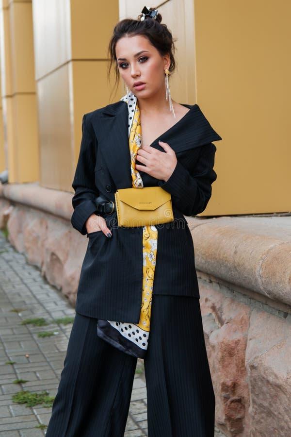 Junges stilvolles Schönheitsmode-modell wirft in der Straße, tragender Pantsuit auf und hat Geldbeutel auf ihrer Taille stockfotografie