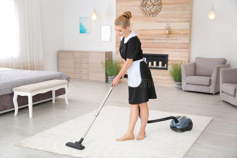 Junges Stubenmädchen, das Schmutz vom Teppich mit Staubsauger entfernt stockbild