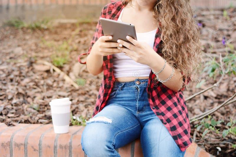 Junges Studentenmädchen mit einer Tablette und einer Kaffeetasse stockfotografie