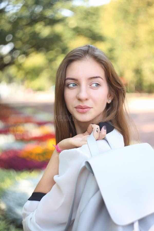Junges Studentenmädchen mit Tasche blickte über ihrer Schulter flüchtig lizenzfreie stockfotos