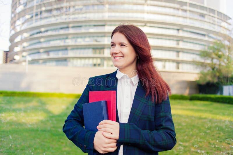Junges Studentenmädchen MSiling, das ein Buch auf einem Hochschulhintergrund hält stockfotografie