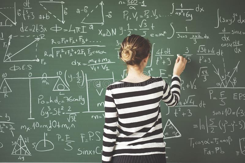 Junges Studentenschreiben mit Kreide auf grünem Kreidebrett im Klassenzimmer stockfoto