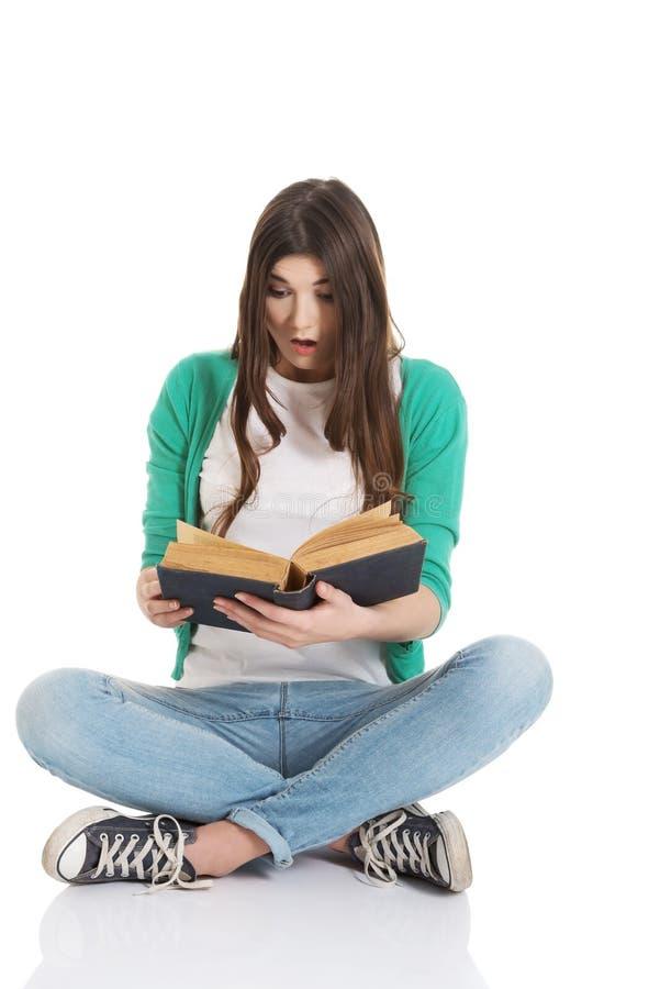 Junges Studentinsitzen und -lesung ein Buch. lizenzfreie stockfotos