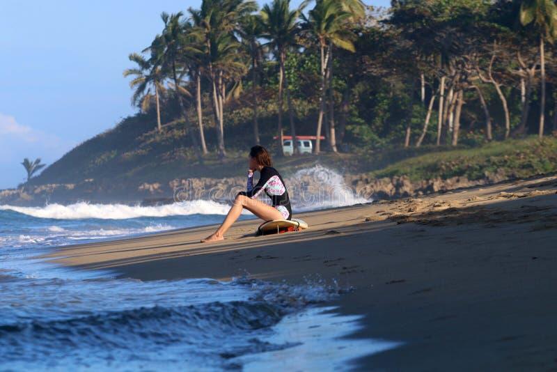 Junges Surfermädchen, das auf dem Strand während des Sonnenuntergangs sitzt stockfotografie