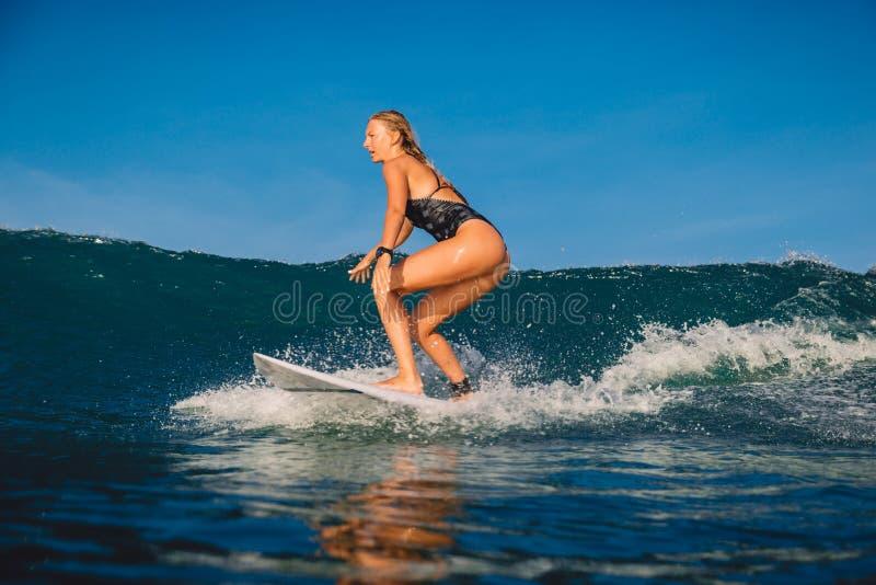 Junges Surfermädchen mit Surfbrett auf Welle lizenzfreies stockbild