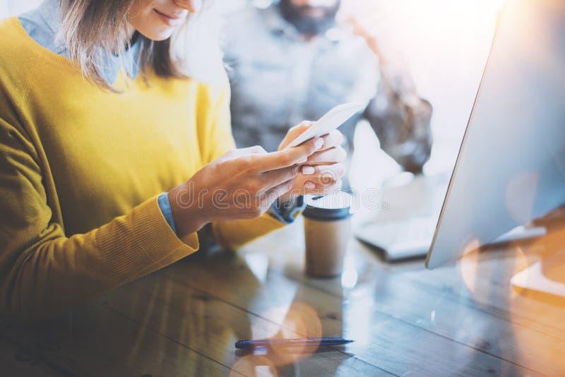 Junges Team von den Mitarbeitern, die im modernen coworking Raum zusammenarbeiten Frau, die Mitteilung mit Smartphone sendet Mann lizenzfreies stockbild