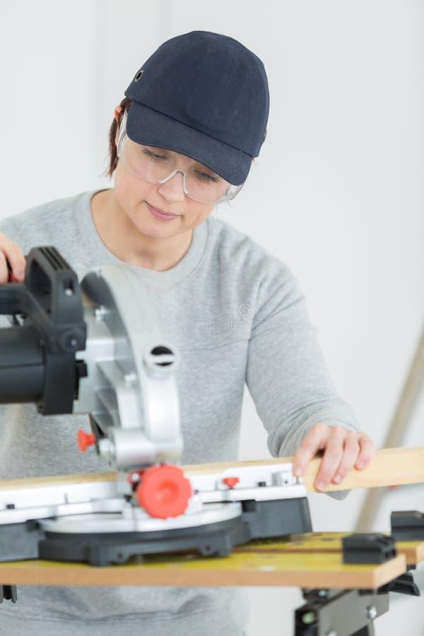 Junges Tischlersschneidebrett der erwachsenen Frau in der Werkstatt lizenzfreie stockbilder