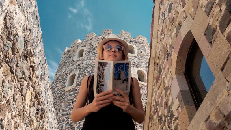 Junges touristisches Mädchen, das eine Broschüre in Rabati-Schloss betrachtet lizenzfreie stockbilder
