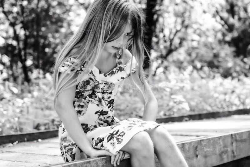 Junges trauriges Mädchenkind allein auf Landwald stockfoto