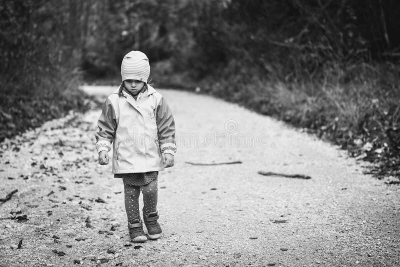 Junges trauriges Mädchenkind geht allein auf Landstraße stockbilder