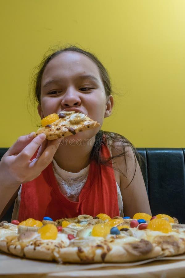 Junges Tweenmädchen, das in Süßigkeits- und Schokoladenpizza beißt stockfotografie
