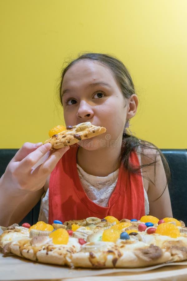 Junges Tweenmädchen, das Süßigkeits- und Schokoladenpizza isst stockbild