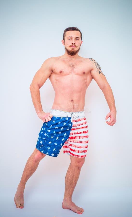 Junges und geeignetes männliches Modell, das seine Muskeln aufwirft stockfoto