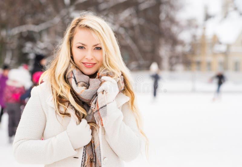 Junges und hübsches Mädchen, das auf Eisbahn im Freien eisläuft lizenzfreies stockbild