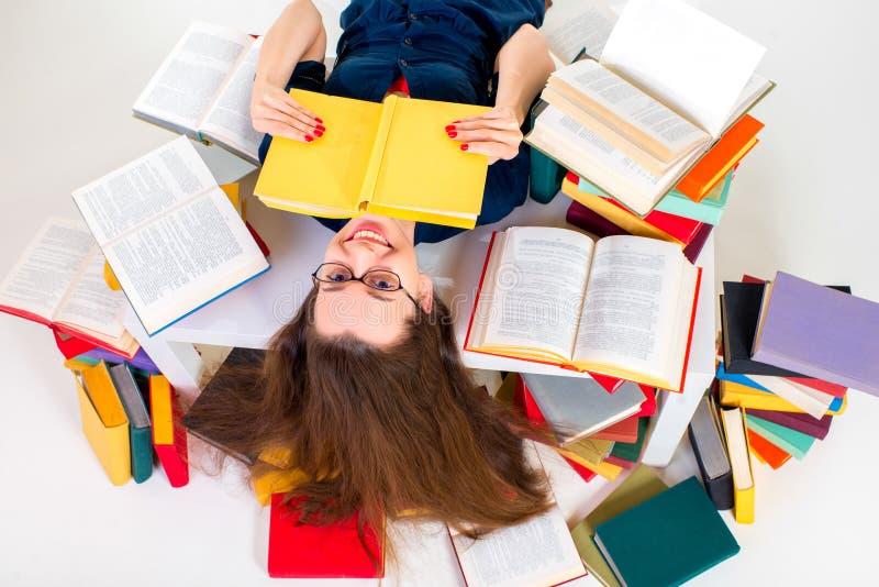 Junges und intelligentes Mädchen, das mit dem Buch umgeben durch buntes Buch liegt stockfotos