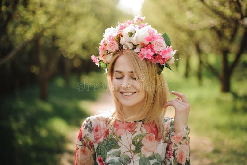 Junges und schönes lächelndes Mädchen in einem Blumendiadem, das unter Bäumen steht stockbild