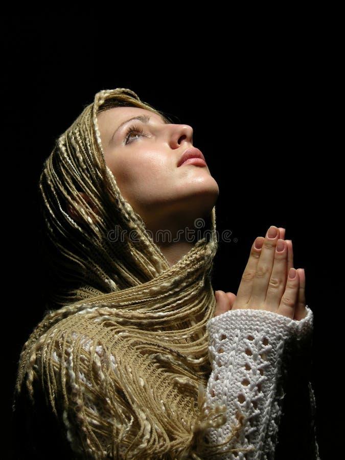Junges und schönes Mädchen, das mit geöffneten Augen betet stockfotos