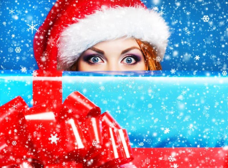 Junges und schönes Mädchen mit einem Weihnachtsgeschenk lizenzfreie stockbilder