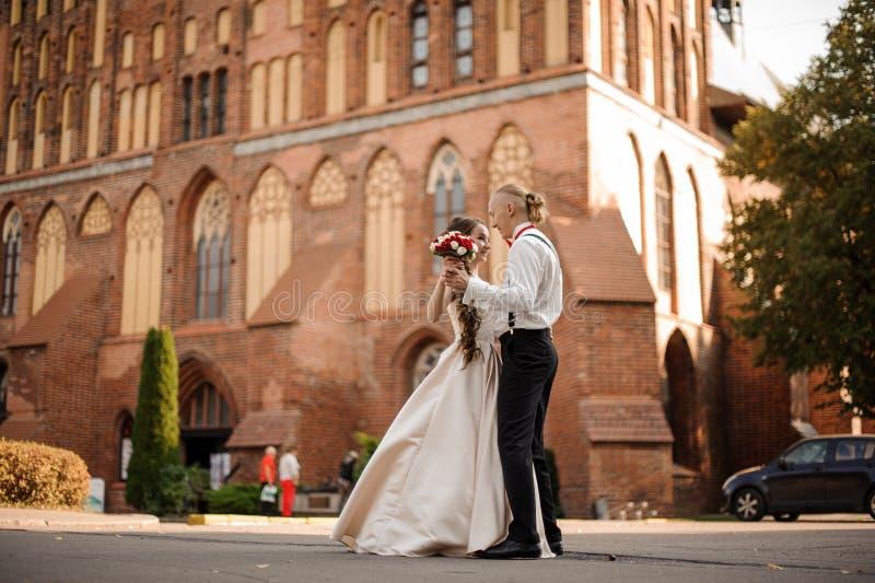 Junges und schönes Tanzen des verheirateten Paars im Hintergrund des Gebäudes des Weinleseroten backsteins mit stockbild