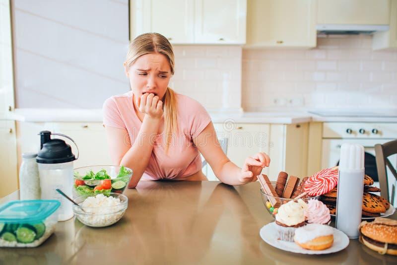 Junges unglückliches dünnes Modell, das Plätzchen auf Tabelle in der Küche berührt Sie betrachtet Seite der ungesunden Fertigkost stockfotografie